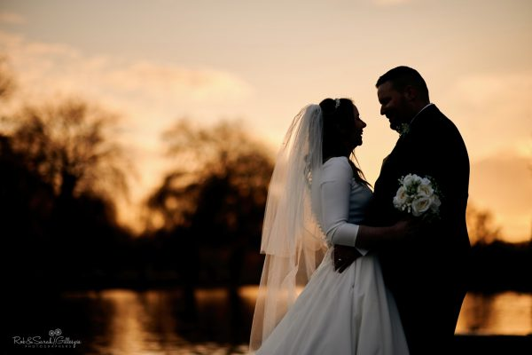 Bride and groom silhouetted against susnet