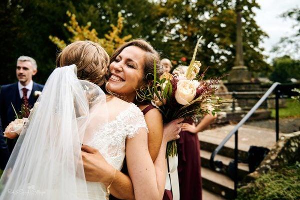 Bridesmaid hugs bride