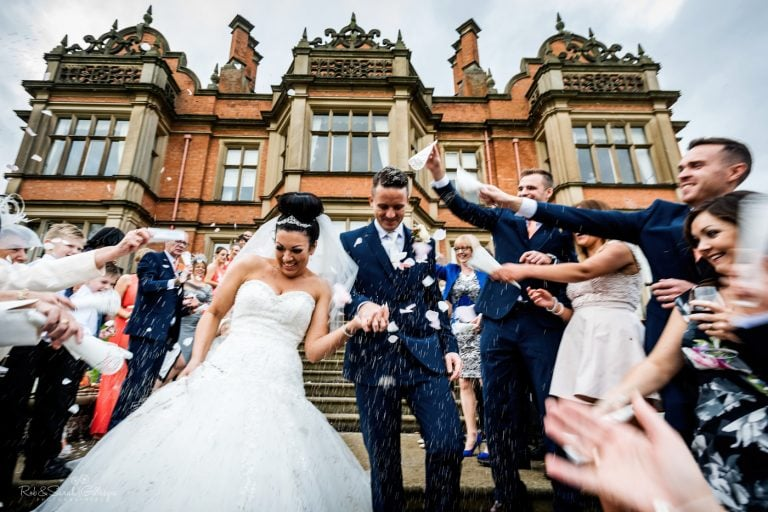 Bride and groom walk down steps as wedding guests throw confetti over them
