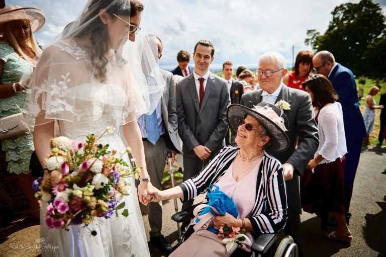 Bride holds hand of wedding guest in wheelchair after church ceremony