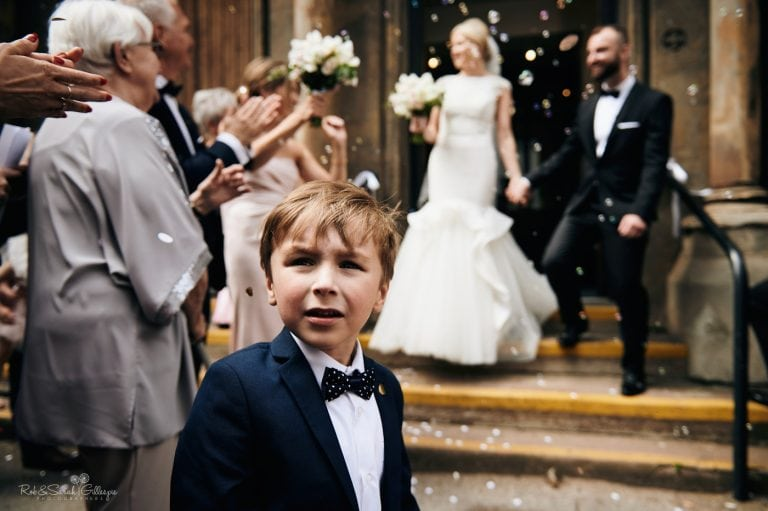 Pageboy looks back as bride and groom have confetti thrown