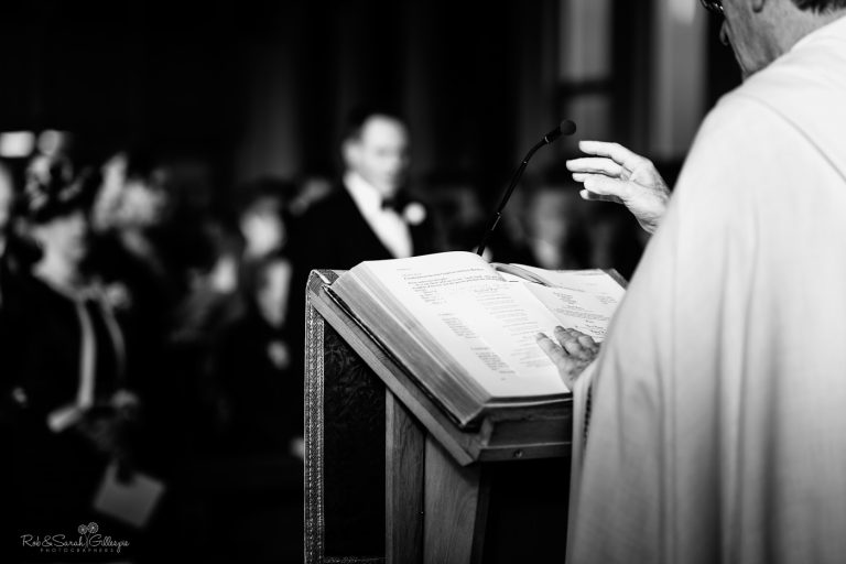 Vicar's hands as he reads from bible during wedding ceremony
