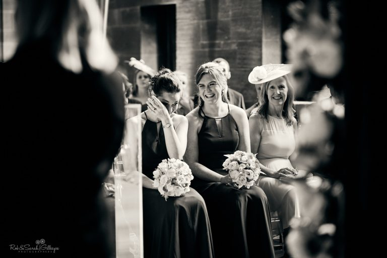 Bridesmaids wiping away tear during wedding ceremony