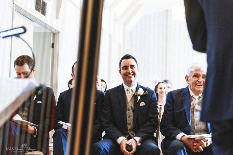 Groomsmen laughing during wedding ceremony