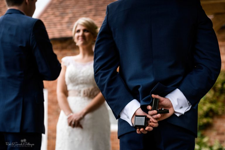 Best man holds wedding rings during ceremony