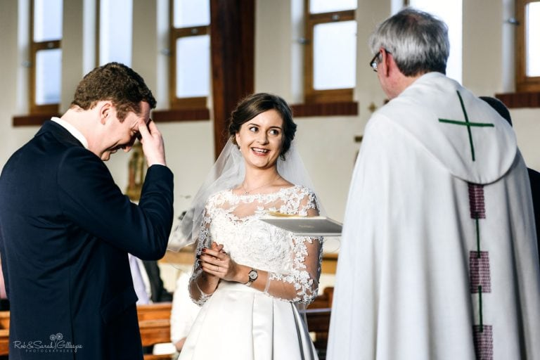 Bride laughing as groom makes mistake during wedding vows