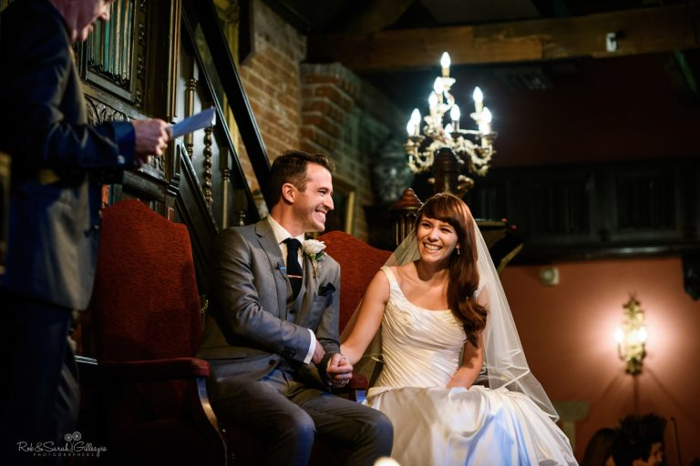 Bride and groom laughing at reading during wedding