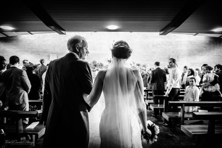 Father glances at daughter as he walks up the aisle for wedding