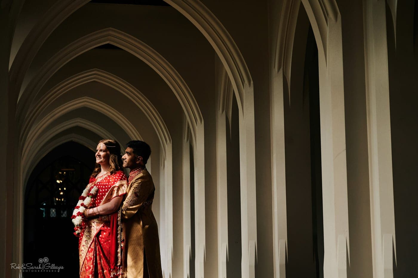 Bride and groom in arched cloisters with strong directional light