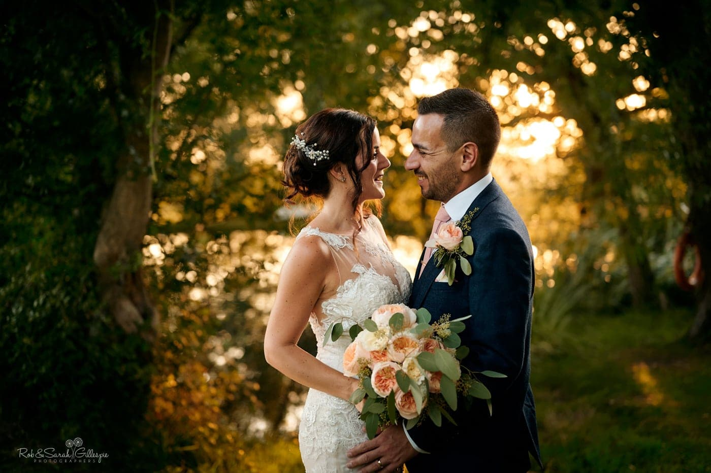 Bride and groom in woodland with beautiful sunset through trees
