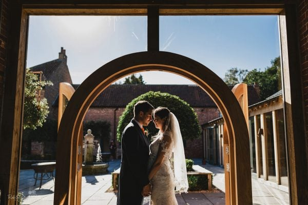 Bride and groom standing on arched doorway of barn venue