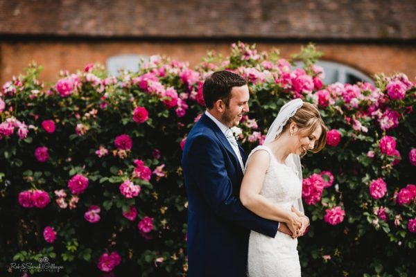 Bride and groom relaxed in front of flower wall