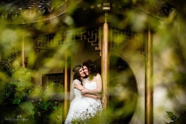 Two brides under ornamental building in garden