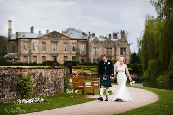 Bride and groom walking on path in wedding venue grounds