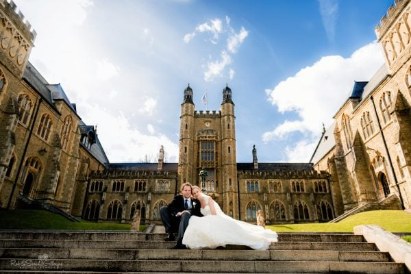 Bride and groom sitting on steps of grand old building