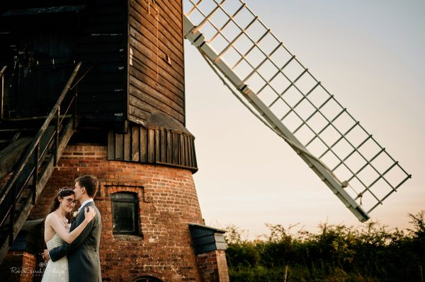 Bride and groom cuddled up by old windmill