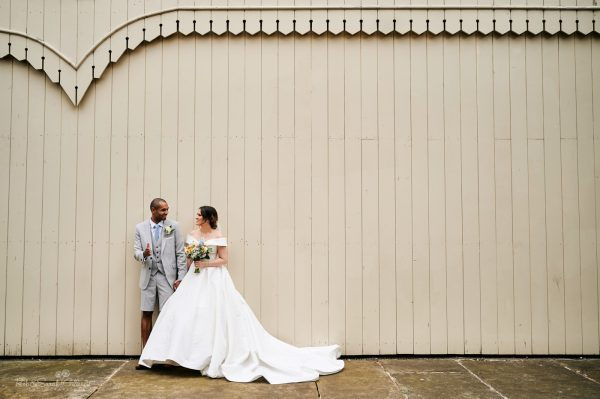 Bride and groom in front of old railway station wooden wall