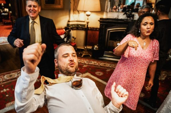 Wedding guest dances with drink balance on his chest