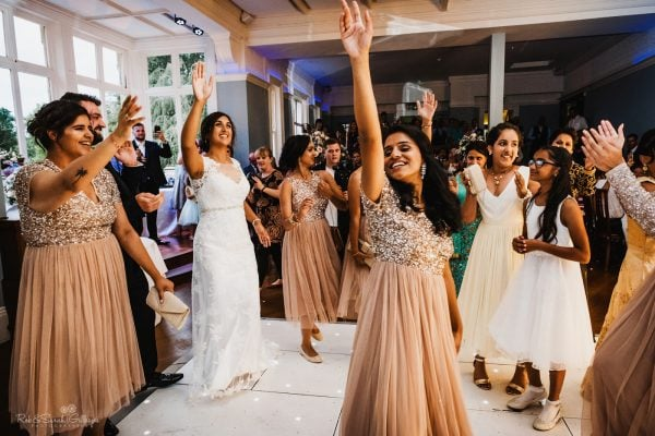 Indian wedding female guests raising hands