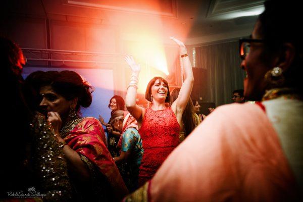 Woman raises hands as she dances at wedding