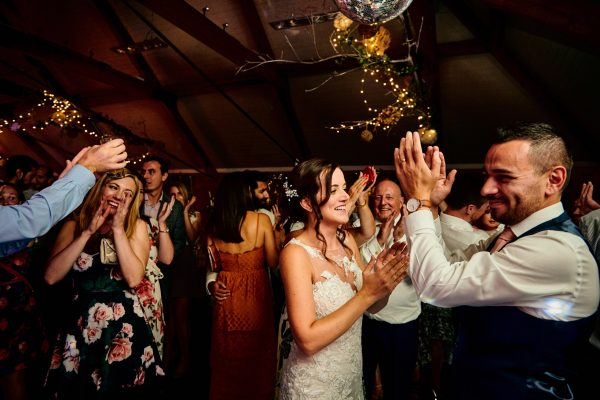 Bride, groom and guests clap during dancing at wedding reception