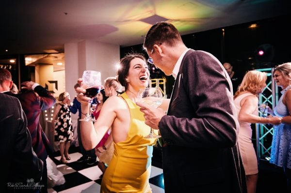 Young couple dance with drinks in hand at wedding