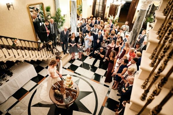 Bride and groom cut wedding cake with guests watching
