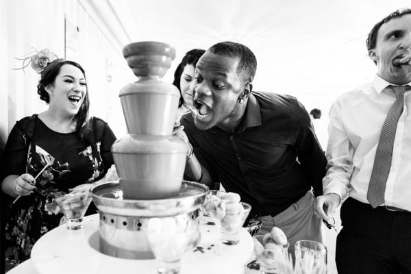 Guests enjoy chocolate fountain at wedding evening party