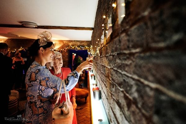 Wedding guest points to old photos on wall for elderly relative