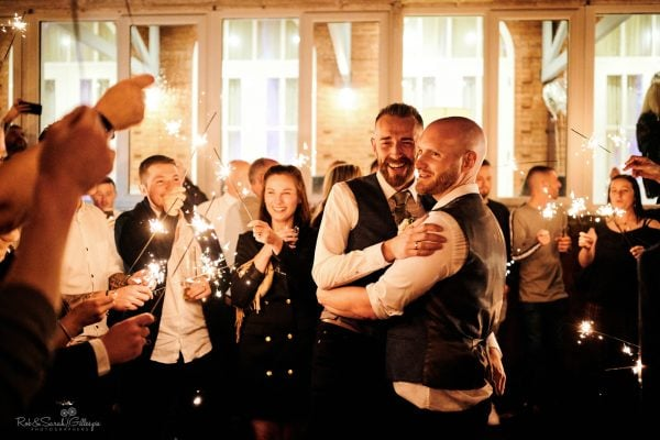 Two grooms surrounded by wedding guests holding sparklers