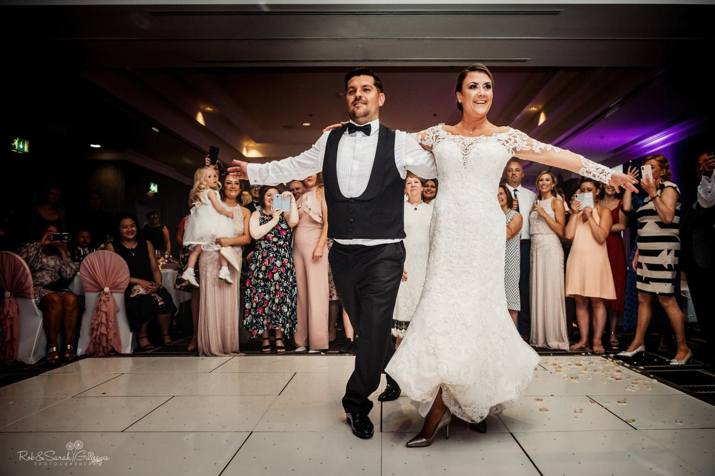 Bride and groom smiling as they perform first dance at wedding