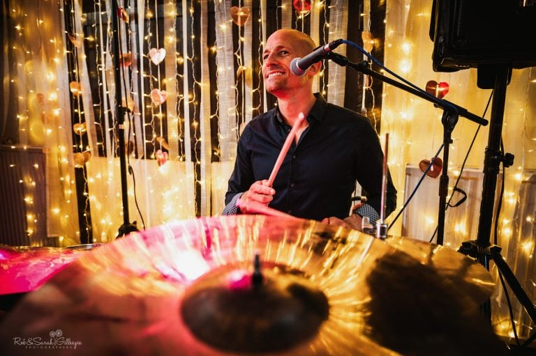 Drummer smiling as her performs with band at wedding party surrounded by lights