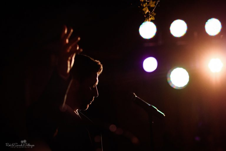 Male singer silhouetted by lights at wedding party