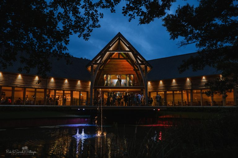 Bride and groom on balcony of barn wedding venue with party happening below