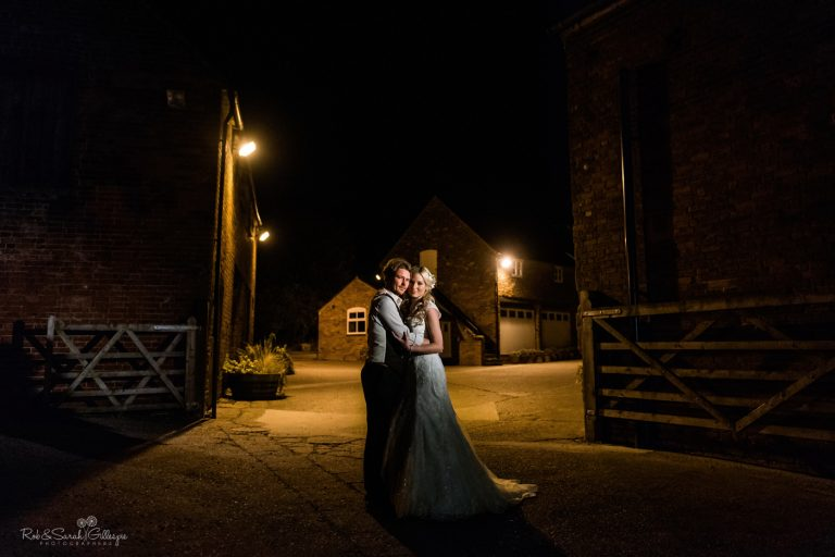 Bride and groom in courtyard at night