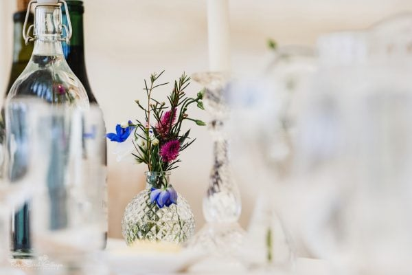 Beautiful flowers in glass vases on table for wedding meal