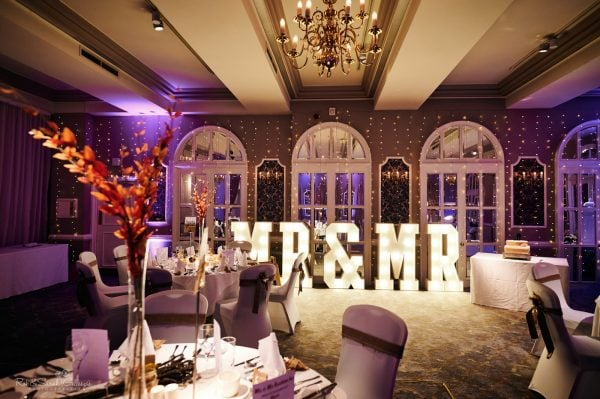 Plush room set up for wedding breakfast with mirrors, lights and exotic flowers