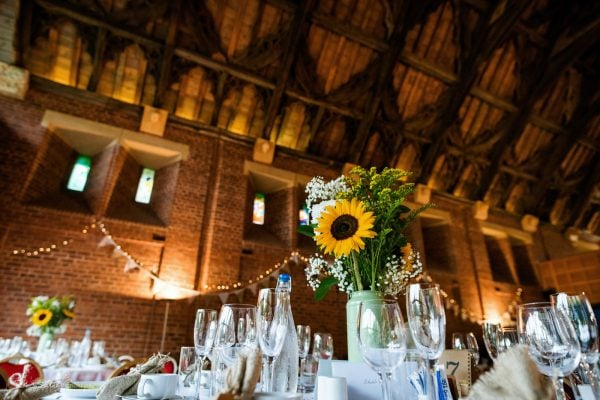 Wedding breakfast details with sunflowers in barn venue