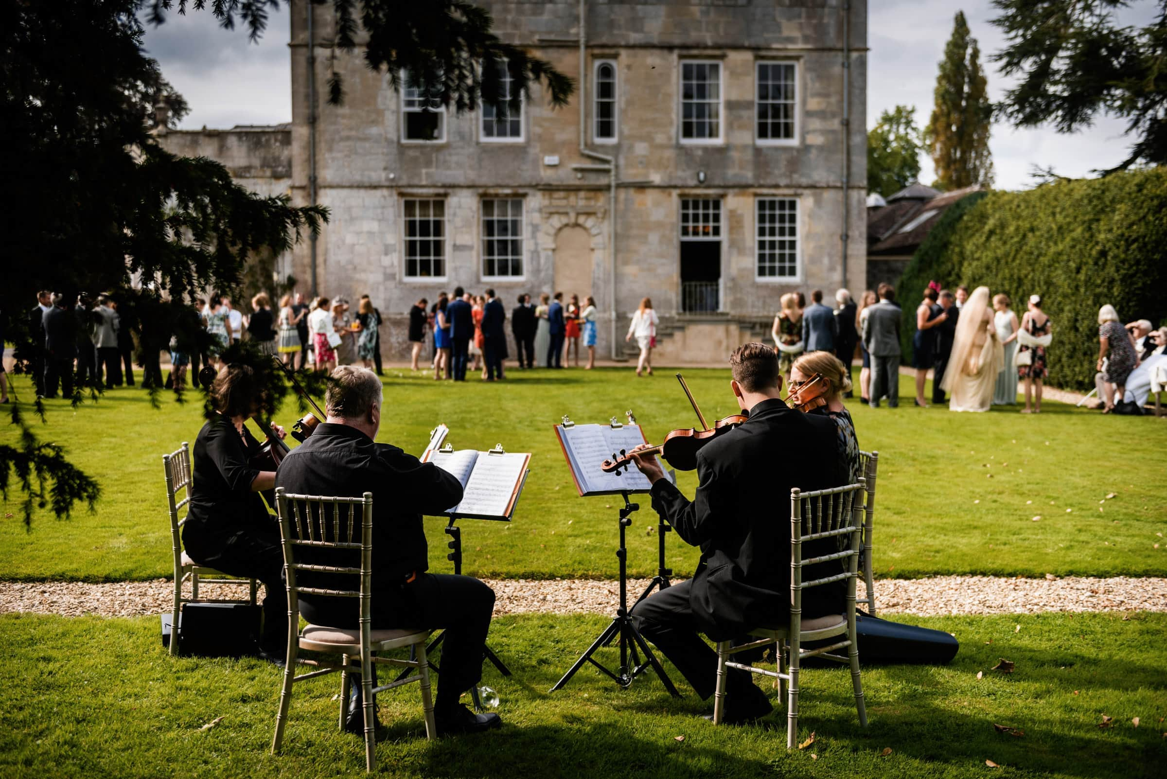 Musicians play during wedding reception with guests on lawn