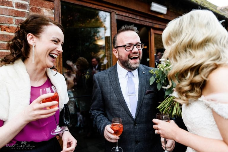 Bride laughing with guests during wedding reception
