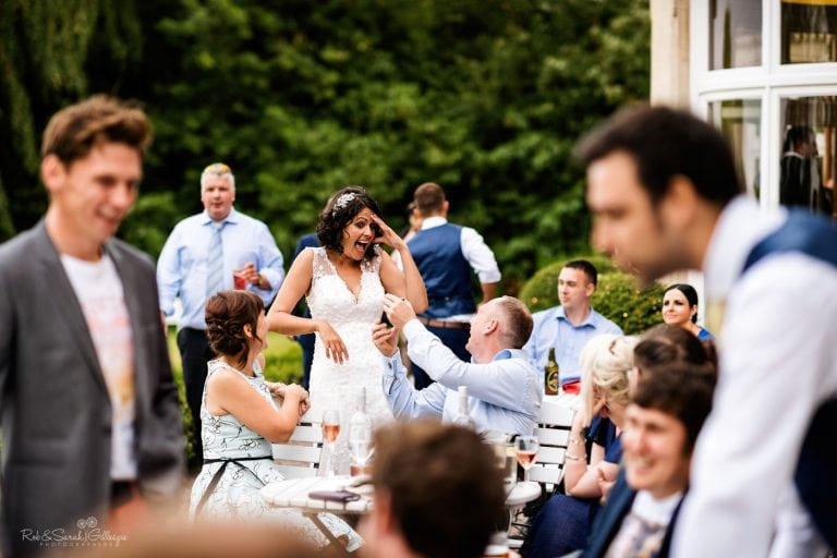 Bride laughing and reacting with wedding guests