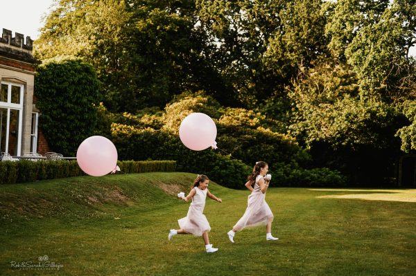 Young bridesmaids running across lawn holding balloons during wedding reception