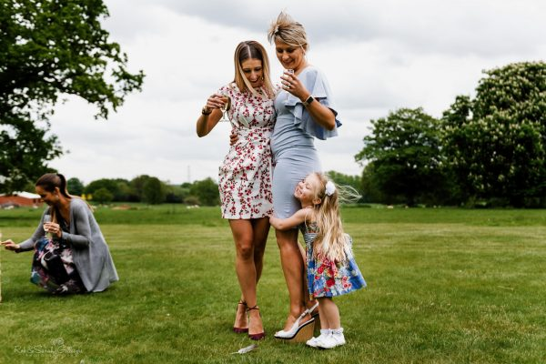 Young girl holds onto mum during wedding reception