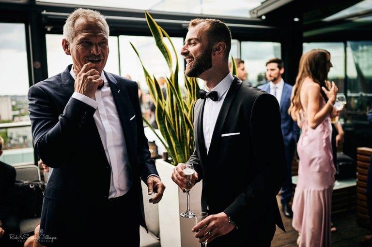 Groom and dad sharing a joke at wedding reception