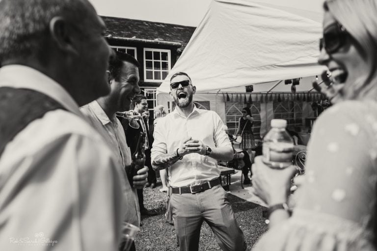 Wedding guest laughing with friends during reception