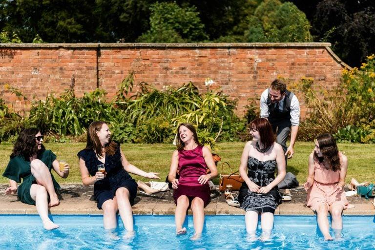Wedding guests soak feet in swimming pool at wedding reception