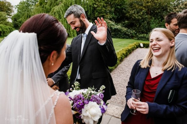 Wedding guests laughing with bride during drinks reception