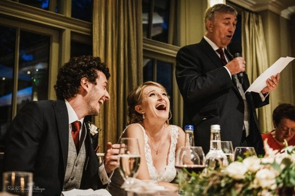 Bride and groom laughing at dad's wedding speech