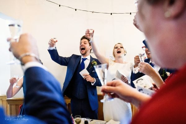 Bride and groom raise glasses to toast during wedding speeches