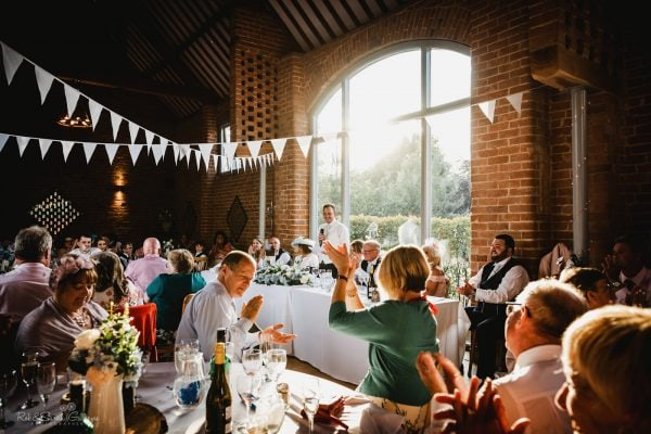Wedding guests clapping at groom's speech in beautiful barn